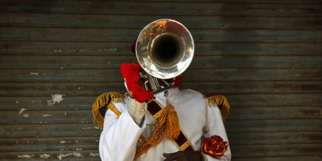 In this Monday, Nov. 3, 2014 photo, Ram Charan, 35, from Bareilly some 256 kilometers (160 miles) from Delhi, a member of Master Band, an Indian brass band specialized in playing weddings, poses for a portrait in New Delhi. Dressed in faded military-style uniforms or long silken tunics and turbans, brass bands playing the latest Bollywood tunes have long been a must-have at any Indian wedding. But as the tastes of young, wealthier Indians shift to more modern music, young couples increasingly choose DJs playing electronic music instead of live bands. The shift is leaving band owners and musicians struggling to find gigs, exacerbating an already difficult existence. (AP Photo /Manish Swarup)