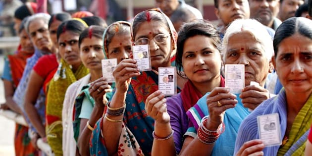 PATNA, INDIA - OCTOBER 28: Voters pose with their ID Cards standing in queue to cast their votes at DAV School, Danapur Cantt, during the third phase of Bihar Assembly Elections on October 28, 2015 in Patna, India. Bihar will hold five-phase elections between October 12 and November 5 to elect the 243-member assembly. Counting of votes will take place on November 8. BJP led NDA and Grand Secular Alliance comprising of RJD, JD (U) and Congress are two main coalitions vying to form the next government in the state. (Photo by Arvind Yadav/ Hindustan Times via Getty Images)