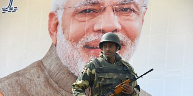 An Indian Border Security Force (BSF) soldier stands guard alongside a poster bearing the image of Indian Prime Minister Narendra Modi near the venue of Modi's scheduled rally in Srinagar on November 6, 2015.   The hardline faction of the Hurriyat Conference, supported by moderate separatists, has announced a 'Million March' on November 7, the day Prime Minister Narindra Modi is scheduled to address a rally in Srinagar.  The state government has launched a massive crackdown on separatist leaders ahead of Prime Minister Modi's visit to the state, with all prominent separatist leaders either detained or put under house arrest, forces deployed in large numbers and barricades erected at sensitive areas.   AFP PHOTO/ Tauseef MUSTAFA        (Photo credit should read TAUSEEF MUSTAFA/AFP/Getty Images)
