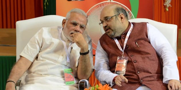 Bharatiya Janata Party (BJP) President Amit Shah (R) talks with Indian Prime Minister Narendra Modi at a BJP National Council meeting at Jawaharlal Nehru Stadium in New Delhi on August 9, 2014.   Leaders of India's ruling Bharatiya Janata Party called on followers to gear up for key state elections in order to extend the Hindu nationalist movement's grip on the country.   AFP PHOTO/RAVEENDRAN        (Photo credit should read RAVEENDRAN/AFP/Getty Images)