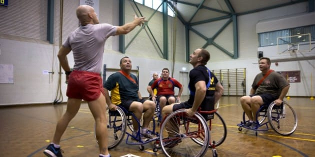 DARWIN, AUSTRALIA - APRIL 15: In this handout photo provided by the Australian Defence Force, Australian Army physical training instructor Corporal Todd Hayes tosses the ball into play during a game of wheelchair AFL attended by Prince Harry at the Soldier Recover Centre, Robertson Barracks on April 15, 2015 in Darwin, Australia. Prince Harry has spent his first two weeks secondment in the Australian Army with the North-West Mobile Force (NORFORCE) and the 1st Brigade. (Photo by CPL Oliver Carter/Australian Defence Force via Getty Images)