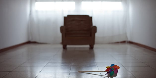 Toy windmill lying on floor of an empty room with sofa and two windows on background.