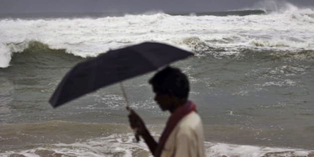 """An Indian local villager walks with his umbrella at Gopalpur beach in Ganjam district 215 kilometers (136 miles) away from the eastern Indian city of Bhubaneswar, India, Friday, Oct. 11, 2013. The Indian Meteorological Department warned that a massive cyclone Phailin was a """"very severe cyclonic storm"""" that was expected to hit India's eastern seaboard with maximum sustained winds of 210-220 kilometers (130-135 miles) per hour. (AP Photo/Biswaranjan Rout)"""