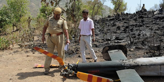 An Indian policeman (L) and a technician from Pawan Hans Helicoptre company collect evidence at the site of the May 13 Indian Border Security Force (BSF) helicopter crash in Rajasthan's Sirohi district, on May 14, 2011. A BSF helicopter crashed May 13 in a hilly region of Rajasthan's Sirohi district, killing all the four of its occupants, a report said. AFP PHOTO/ Sam PANTHAKY (Photo credit should read SAM PANTHAKY/AFP/Getty Images)