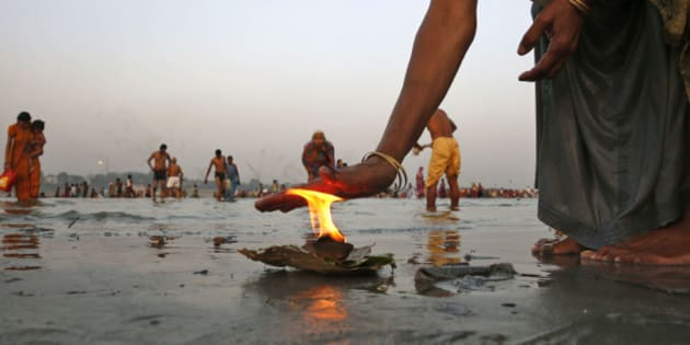 An Indian Hindu devotee offers prayers with a lamp, as others take holy dips at Sangam, the confluence of the Rivers Ganges, Yamuna and the mythical Saraswati, in Allahabad, India, Thursday, May 28, 2015. Hindus across the country are celebrating Ganga Dussehra, devoted to the worship of the River Ganges. (AP Photo/Rajesh Kumar Singh)