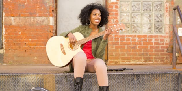Mixed race woman playing guitar in city
