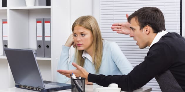 Businessman is sitting in office with his secretary and he is very angry at her because of something.