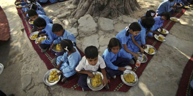 Indian schoolchildren eat a free midday meal, provided on all working days at a government school on the outskirts of Jammu, India, Tuesday, Oct. 9. The United Nations now says its 2009 headline-grabbing announcement that 1 billion people in the world were hungry was off-target and that the number is actually more like 870 million. (AP Photo/Channi Anand)