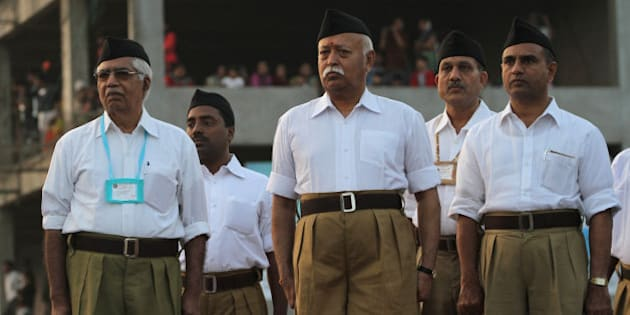 Mohan Bhagwat, chief of the militant Hindu group Rashtriya Swayamsevak Sangh (RSS), center, watches volunteers march during a three-day workers camp on the outskirts of Ahmadabad, India, Saturday, Jan. 3, 2015. The RSS, parent organization of the ruling Bharatiya Janata Party, combines religious education with self-defense exercises. The organization has long been accused of stoking religious hatred against Muslims. (AP Photo/Ajit Solanki)