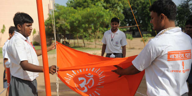 Senior Bajrang Dal volunteers fold with respect the Bajrand Dal Flag at a youth camp on the outskirts of Ahmedabad in the early morning of May 17, 2012.  Some 168 students, 18 instructors and 15 organisers are participating in a Bajrang Dal Basic Youth Camp from May 13 - 20.  Bajrang Dal, a hardline Hindu organization in India, is the youth wing of the Vishwa Hindu Parishad (VHP) and is based on the ideology of Hindutva. Apart from safeguarding 'holy cows', other goals include protecting India's Hindu identity from the perceived dangers of communalism, Muslim demographic growth and Christian conversion.   AFP PHOTO / Sam PANTHAKY        (Photo credit should read SAM PANTHAKY/AFP/GettyImages)