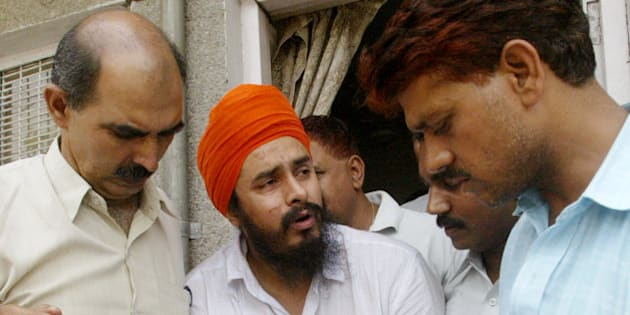 Jagtar Singh Hawara, center, chief of Sikh separatist Babbar Khalsa, reacts in pain as he is shown to the media by police officers of the Crime Branch in New Delhi, India, Wednesday, June 8, 2005. Hawara and two other associates were arrested for their alleged role in the May 22 twin blasts that killed at least one person and wounded 50 at two theaters in New Delhi showing a film condemned by Sikh religious leaders. (AP Photo/Gurinder Osan)