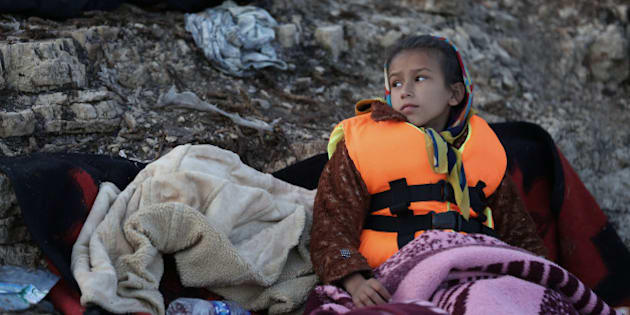 A child looks around as migrants prepare to travel by dinghy to the Greek island of Chios, from Turkish coast near Cesme, Izmir, Turkey, Thursday, Nov. 5, 2015. More than 300,000 people have traveled on dinghies and boats from nearby Turkey to Greek islands this year, with dozens dying along the way. (AP Photo/Emre Tazegul)