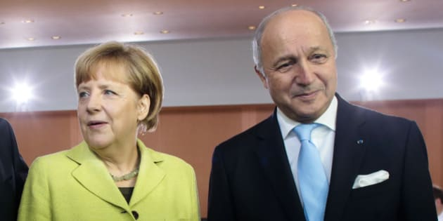 German Chancellor Angela Merkel, left, welcomes French Foreign Minister Laurent Fabius, right, for the German government's cabinet meeting at the chancellery in Berlin, Wednesday, Oct. 15, 2014. Laurent Fabius attends the cabinet meeting as a guest. (AP Photo/Markus Schreiber)