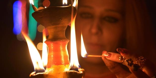 An Indian woman lights an earthen lamp in Amritsar on November 10, 2015 on the eve of the Indian festival of Diwali. Diwali, the Festival of Lights, marks victory over evil and commemorates the time when Hindu god Lord Rama achieved victory over Ravana and returned to his kingdom Ayodhya.  AFP PHOTO / NARINDER NANU        (Photo credit should read NARINDER NANU/AFP/Getty Images)