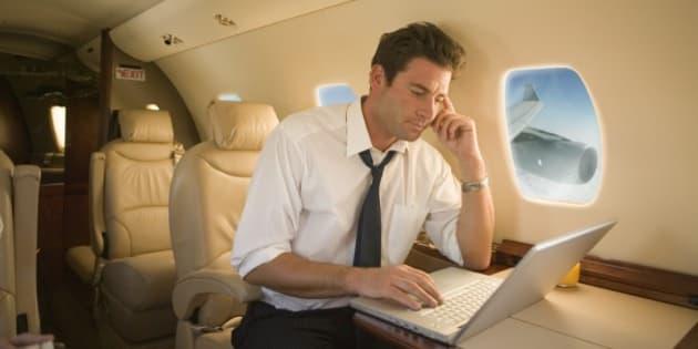 Businessman using laptop on airplane