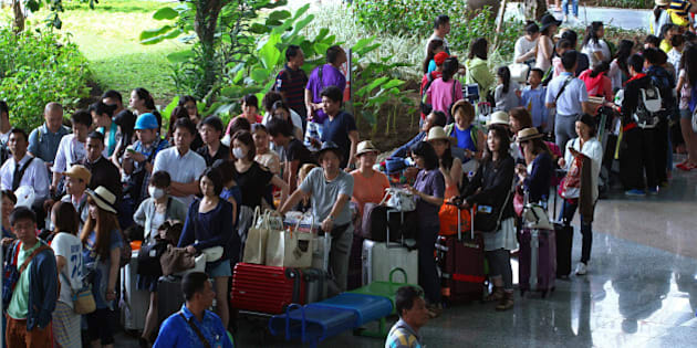 Passengers line up after their flights were canceled at Bali's international airport, in Denpasar, Indonesia, Friday, July 10, 2015. Ash spewing from a volcano on Indonesia's main island of Java has sparked chaos for holidaymakers as airports close and international airlines cancel flights to tourist hotspot Bali, stranding thousands. (AP Photo/Firdia Lisnawati)