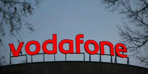 The Vodafone logo sits illuminated on top of the Vodafone Group Plc regional offices in Berlin, Germany, on Thursday, Nov. 5, 2015. Liberty Global and Vodafone ended talks about an exchange of assets -- the companies' operations overlap the most in the U.K., Germany and the Netherlands -- denying the cable and mobile-phone giants a chance to consolidate in their key markets. Photographer: Krisztian Bocsi/Bloomberg via Getty Images
