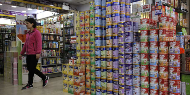 "In this Friday, April 10, 2015 photo, a woman walks past cans of baby formula stacked in a shop at a district regarded as a hub of ""parallel trading"" near the Chinese border in Hong Kong. Eighteen years after this world financial hub returned from colonial British control to Chinese rule, many say they feel more alienated and less trusting than ever of the central Chinese government and even the people visiting from across the border. Called ""parallel trading"" because it happens in a gray area alongside legal trade, such commerce has become an especially visible target of Hong Kongers' anger. Chinese visitors cross into the city, which has no sales tax and a reputation for authentic goods, to buy up baby formula, smartphones, luxury goods, diapers and medicine and then resell them at a profit in the mainland, warping the local economy and causing shortages. (AP Photo/vincent Yu)"