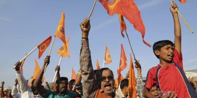 Supporters of right-winged Vishwa Hindu Parishad (VHP) or World Hindu Council raise flags and shout slogans during a rally organized as part of VHP's 50th anniversary celebrations in Bangalore, India, Sunday, Feb. 8, 2015. (AP Photo/Aijaz Rahi)