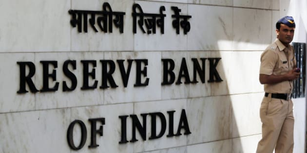 A police officer stands beside Reserve Bank of India (RBI) signage at the central bank's headquarters in Mumbai, India, on Tuesday, April 1, 2014. Indias central bank left its key interest rate unchanged as consumer-price inflation eased to a two-year low and the rupee strengthened, increasing scope to support growth ahead of national elections starting this month. Photographer: Vivek Prakash/Bloomberg via Getty Images
