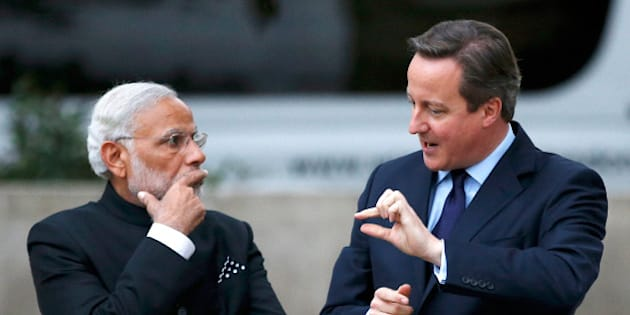 LONDON, UNITED KINGDOM - NOVEMBER 12:  Prime Minister David Cameron and India's Prime Minister Narendra Modi chat after paying a visit to the statue of Mahatma Ghandi in Parliament Square during an official three day visit on November 12, 2015 in London, England. In his first trip to Britain as Prime Minister Modi's visit will aim to develop economic ties between the two countries. In a busy schedule he is due to speak at Wembley Stadium, lunch with the Queen at Buckingham Palace, address Parliament and stay overnight at Chequers. (Photo by Peter Nicholls - WPA Pool/Getty Images)