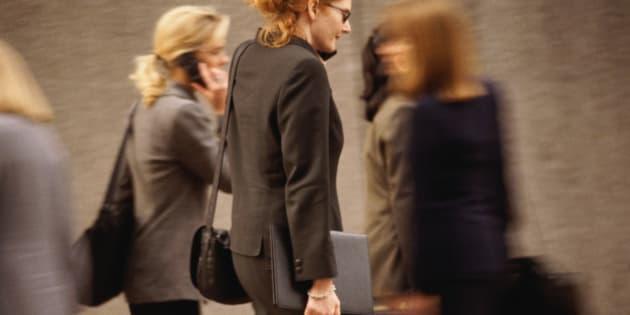Woman talking on cellular phone, walking in crowd of women