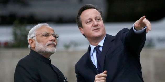 Britain's Prime Minister David Cameron, right, and India's Prime Minister Narendra Modi watch a flypast by the Royal Air Force's Red Arrow display team as they visit  the statue of Mahatma Ghandi in Parliament Square, in London, Thursday  Nov. 12, 2015. Modi is on a 3 day visit to Britain. (Peter Nicholls, Pool via AP)