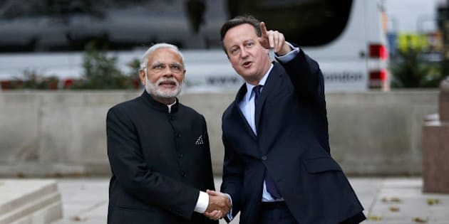 Britain's Prime Minister David Cameron (R) and India's Prime Minister Narendra Modi (L) watch a flypast by the Royal Air Force Red Arrows display team in Parliament square in London on November 12, 2015. India's Prime Minister Narendra Modi will meet Britain's Queen Elizabeth II and address a huge rally at London's Wembley Stadium during a three-day visit to Britain focused on trade and investment starting today. AFP PHOTO / POOL / PETER NICHOLLS        (Photo credit should read PETER NICHOLLS/AFP/Getty Images)