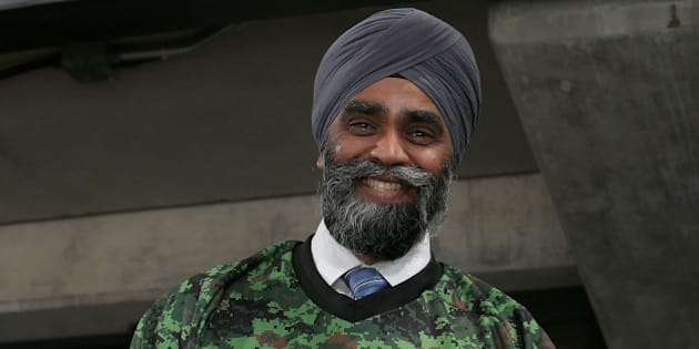 OTTAWA, ON - NOVEMBER 12: The newly elected Canadian Minister of National Defence, The Honourable Harjit Sajjan  hams it up while wearing a Sens Camouflage jersey prior to the start of an NHL game between the Ottawa Senators and the Vancouver Canucks on Canadian Forces Appreciation Night during an NHL game at Canadian Tire Centre on November 12, 2015 in Ottawa, Ontario, Canada.  (Photo by Jana Chytilova/Freestyle Photography/Getty Images)