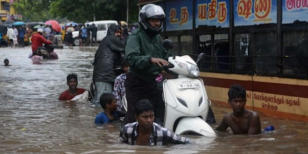 Indian men make their way on a flooded street in Chennai on November 9, 2015 following heavy rain from an approaching cyclonic system off the coast. Indian meteorological authorities have issue issued a cyclone alert for the Bay of Bengal coast in Tamil Nadu. AFP PHOTO        (Photo credit should read STR/AFP/Getty Images)
