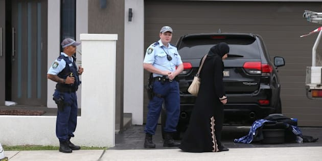 Police talk to a woman outside a property in the suburb of Merrylands in Sydney, Wednesday, Oct. 7, 2015. Police arrested four people during a series of raids Wednesday in connection with the slaying of a civilian police worker, which officials have said they believe was linked to terrorism. (AP Photo/Rick Rycroft)