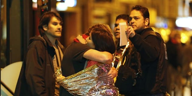 People hug each other before being evacuated by bus, near the Bataclan concert hall in central Paris, on November 14, 2015. More than 100 people were killed in a mass hostage-taking at a Paris concert hall on November 13 and many more were feared dead in a series of bombings and shootings, as France declared a national state of emergency.      AFP PHOTO / FRANCOIS GUILLOT        (Photo credit should read FRANCOIS GUILLOT/AFP/Getty Images)