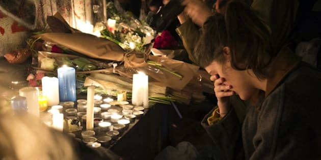 A woman reacts in front of candles in tribute to the victims of the deadly Paris' attacks on November 14, 2015 at the Place de la Republique in Paris. Islamic State jihadists claimed a series of coordinated attacks by gunmen and suicide bombers in Paris on November 13 that killed at least 129 people in scenes of carnage at a concert hall, restaurants and the national stadium. AFP PHOTO / JOEL SAGET        (Photo credit should read JOEL SAGET/AFP/Getty Images)
