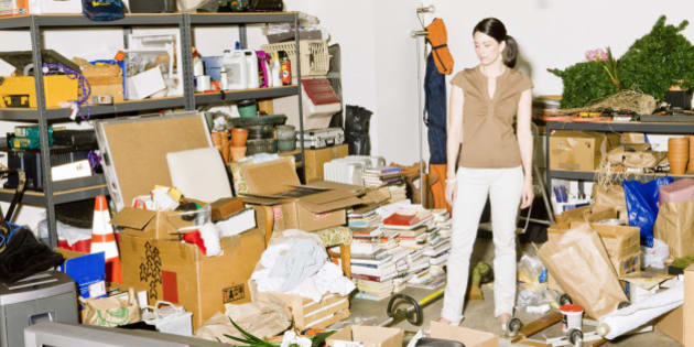 Frustrated woman looking at clutter in garage