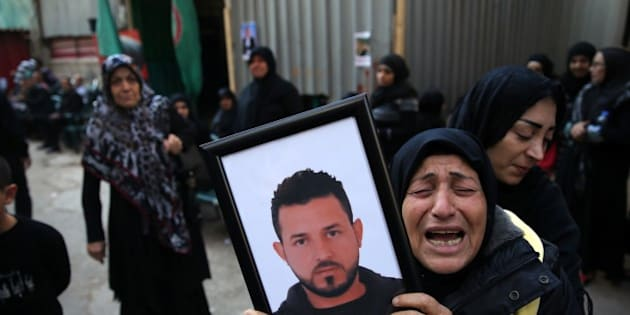 A relative of Samer Huhu, who was killed in a twin bombing attack that rocked a busy shopping street in the area of Burj al-Barajneh, waves his portrait as she mourns during his funeral in the southern suburb of the capital Beirut on November 13, 2015. Lebanon mourned 44 people killed in south Beirut in a twin bombing claimed by the Islamic State group, the bloodiest such attack in years, the Red Cross also said at least 239 people were also wounded, several in critical condition. AFP PHOTO/JOSEPH EID        (Photo credit should read JOSEPH EID/AFP/Getty Images)