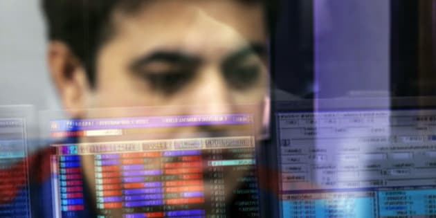 An employee is reflected in a glass panel as he monitors securities on a computer monitor at a brokerage firm in Mumbai, India, on Tuesday, Aug. 25, 2015. Indian stocks advanced in volatile trading a day after the benchmark gauge plunged the most in six years, as banks helped counter declines in software exporters. Photographer: Dhiraj Singh/Bloomberg via Getty Images
