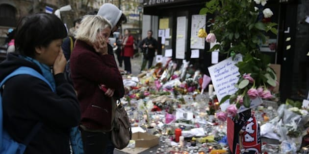 People spend a moment mourning the dead at the site of the attack at the Cafe Belle Equipe on rue de Charonne in the 11th district, prior to going to work early on November 16, 2015 in Paris, three days after the terrorist attacks that left over 130 dead and more than 350 injured. France prepared to fall silent at noon on November 16 to mourn victims of the Paris attacks after its warplanes pounded the Syrian stronghold of Islamic State, the jihadist group that has claimed responsibility for the slaughter.  AFP PHOTO / KENZO TRIBOUILLARD        (Photo credit should read KENZO TRIBOUILLARD/AFP/Getty Images)