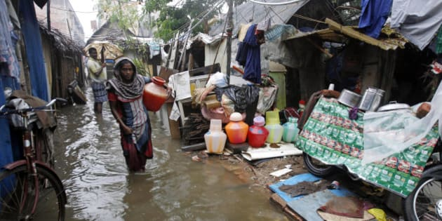 An Indian woman carries a vessel of water at a slum dwelling as it rains in Chennai, India, Friday, Nov. 13, 2015. Heavy rains lashed Chennai and other parts of Tamil Nadu state Friday, throwing life out of gear and disrupting train and flight schedules even as dozens were killed in rain related incidents, according to news reports. The Indian Meteorological Department has warned of more rains over the weekend. (AP Photo/Arun Sankar K)