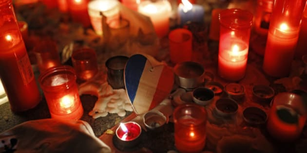 A wooden heart with the colours of the French flag rests among candles placed by people outside the French embassy in Madrid, Monday, Nov. 16, 2015. France is urging its European partners to move swiftly to boost intelligence sharing, fight arms trafficking and terror financing, and strengthen border security in the wake of the Paris attacks. (AP Photo/Francisco Seco)