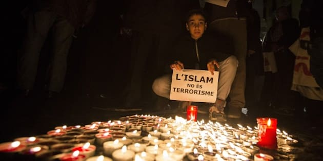 BARCELONA, SPAIN - NOVEMBER 16: Muslims from Barcelona gather to condemn Friday terror attacks in Paris by lighting candles at Placa Sant Jaume in Barcelona, Spain on November 16, 2015. (Photo by Albert Llop/Anadolu Agency/Getty Images)