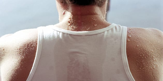 Man in white vest covered in sweat, rear view, close-up