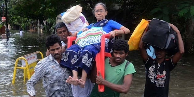 Indian men carry an elderly woman on a flooded street following heavy rain in Chennai on November 16, 2015. Large areas of the southern Indian city of Chennai have been flooded following days of heavy rain. AFP PHOTO        (Photo credit should read STR/AFP/Getty Images)