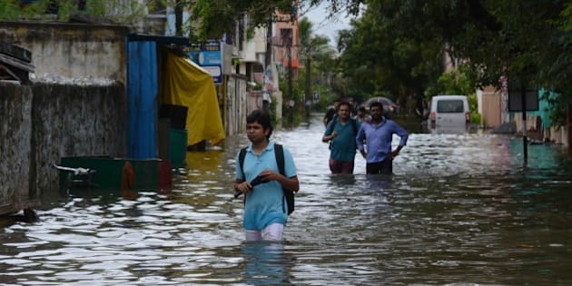 Indian people make their way on a flooded street following heavy rain in Chennai on November 16, 2015.  Large areas of the southern Indian city of Chennai have been flooded following days of heavy rain. AFP PHOTO        (Photo credit should read STR/AFP/Getty Images)