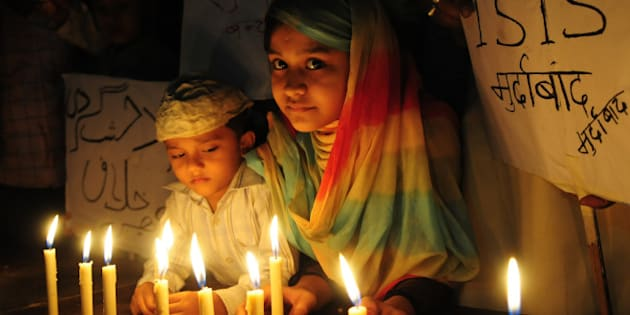 BHOPAL, INDIA - NOVEMBER 15: Muslim kids hold placard with slogans against the ISIS during a candle light vigil to express solidarity with the victims of Paris terror attacks on November 15, 2015 in Bhopal, India. At least 129 people lost their life in terror attacks by terrorists in Paris at the packed Bataclan concert hall, restaurants and bars, and outside the Stade de France national stadium. Islamist jihadist group IS, that has seized control of larges parts of Syria and Iraq, claimed responsibility for the attacks. (Photo by Mujeeb Faruqui/Hindustan Times via Getty Images)