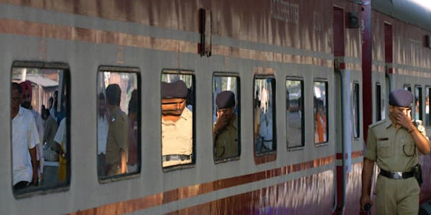 Kolkata, INDIA:  Indian policemen are reflected in a train carriage windows as they walk past the high speed air conditioned 'Rajdhani Express' prior to it's departure from a station in Kolkata, 24 February 2006.   Indian Railway Minister Laloo Prasad Yadav presented the 2006-07 Railway Budget before Members of the Parliament in New Delhi. The Railway Protection Force (RPF) is being modernised to strengthen passenger security in trains with 'special arrangements' being made for women, Yadav said.   AFP PHOTO/Deshakalyan CHOWDHURY  (Photo credit should read DESHAKALYAN CHOWDHURY/AFP/Getty Images)