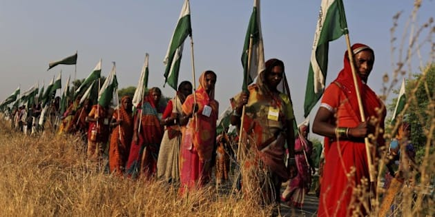 "In this Tuesday, Oct. 9, 2012 photo, Indian landless farmer women march during the ""Jan Satyagraha,"" near Agra, India. Thousands of poor farmers have ended their march to India's capital after the government agreed to formulate a new reform policy, providing land rights to them and fast tracking settlement of their land disputes. The protesters from nearly a dozen states set out on a 320-kilometer (200-mile) march from the central Indian city of Gwalior nine days ago under the banner of ""Ekta Parishad,"" or ""Unity Council,"" and planned to reach New Delhi at the end of the month. (AP Photo/Kevin Frayer)"