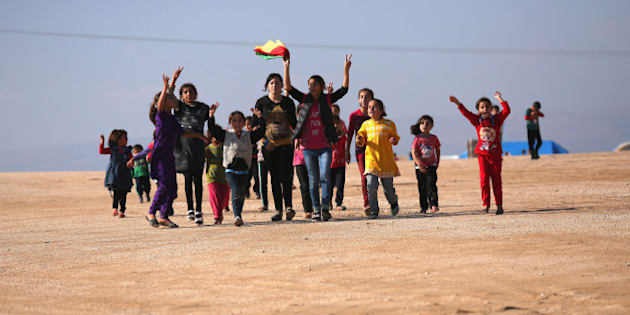 DEREK, SYRIA - NOVEMBER 13:  Yazidi refugees celebrate news of the liberation of their homeland of Sinjar from ISIL extremists, while at a refugee camp on November 13, 2015 in Derek, Rojava, Syria. Kurdish Peshmerga forces in Iraq say they have retaken Sinjar, with the help of airstrikes from U.S. led coalition warplanes. The Islamic State captured Sinjar in August 2014, killing many and sexually enslaving thousands of Yazidi women.  (Photo by John Moore/Getty Images)