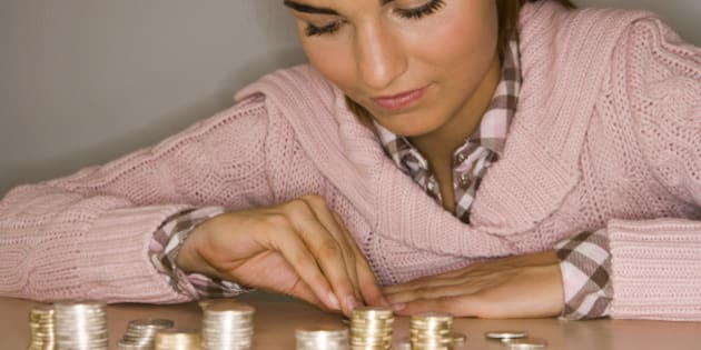 young girl sitting with piles of coins