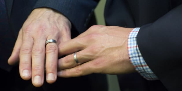Men's hands together showing wedding rings
