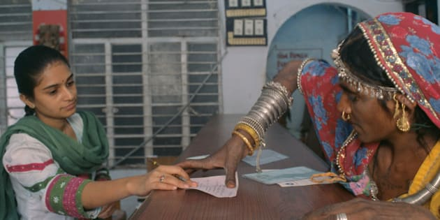 Rural Woman Putting A Thumb Impression In A Bank To Open Her Bank Account At Bank, Ahmedabad,India. (Photo by Education Images/UIG via Getty Images)